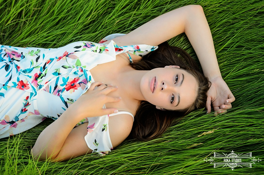 Loveland High School senior photos of girl laying down in green grass.