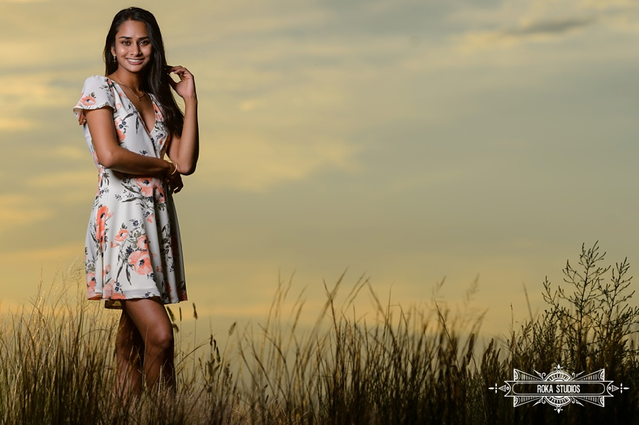 senior picture with golden light, clouds, and tall grass.