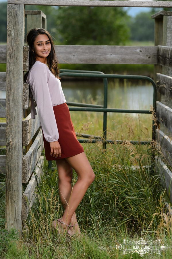 senior pictures of a girl next to rustic wooden fence and lake